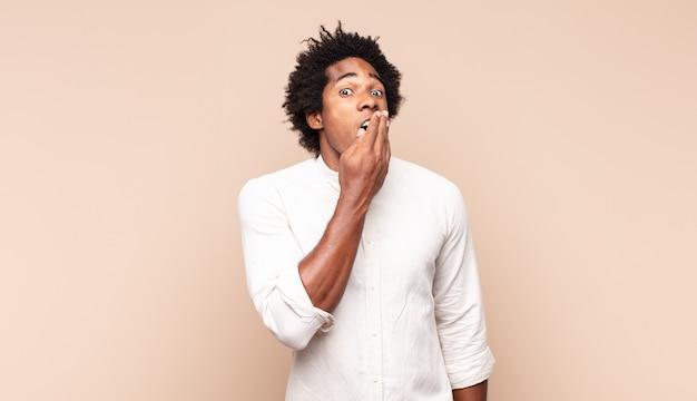 Jovem homem afro bocejando preguiçosamente no início da manhã, acordando e parecendo sonolento, cansado e entediado