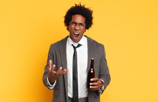 Jovem homem afro parecendo zangado, irritado e frustrado gritando wtf ou o que há de errado com você