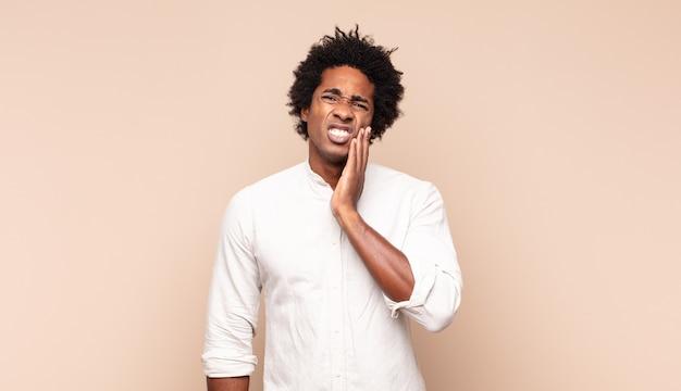 Jovem homem afro segurando a bochecha e sofrendo de uma forte dor de dente, sentindo-se doente, infeliz e miserável, procurando um dentista