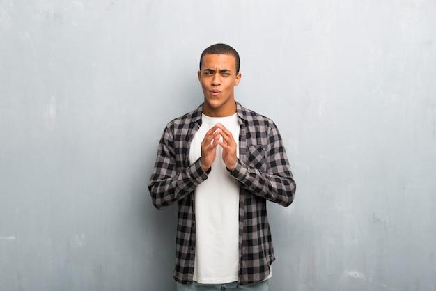 Jovem, homem americano africano, com, camisa checkered, esquematizar, algo