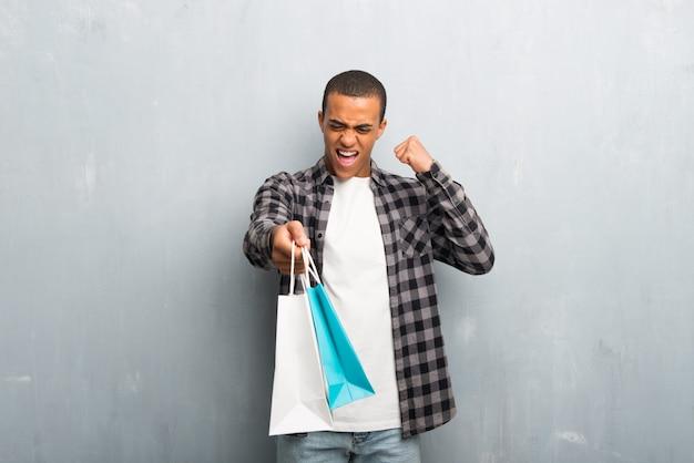 Jovem, homem americano africano, com, camisa checkered, segurando, um, muitos, bolsas para compras