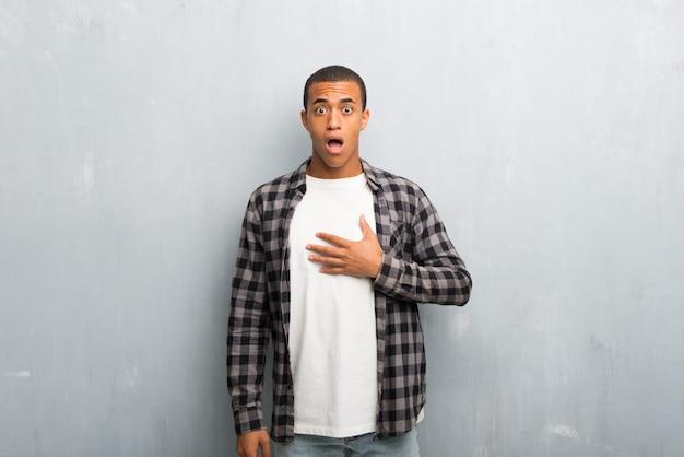 Jovem, homem americano africano, com, camisa checkered, surpreendido, e, chocado, enquanto, olhar, direita