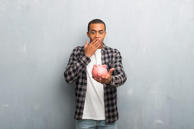 Jovem, homem americano africano, com, camisa checkered, surpreendido, enquanto, prendendo um, grande, piggybank