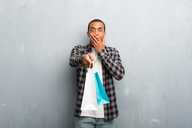 Jovem, homem americano africano, com, camisa checkered, surpreendido, enquanto, segurando, um, muitos, bolsas para compras