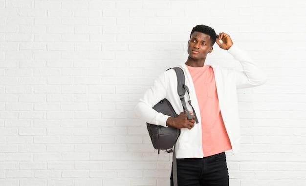 Jovem, homem americano africano, estudante, tendo, dúvidas, e, com, confundir, rosto, expressão, enquanto, cabeça raspando
