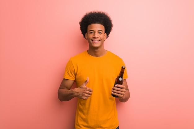 Jovem, homem americano africano, segurando, um, cerveja, divertimento, e, feliz, fazendo, um, gesto, de, vitória
