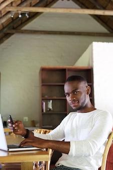 Jovem, homem americano africano, sentando tabela, com, telefone móvel