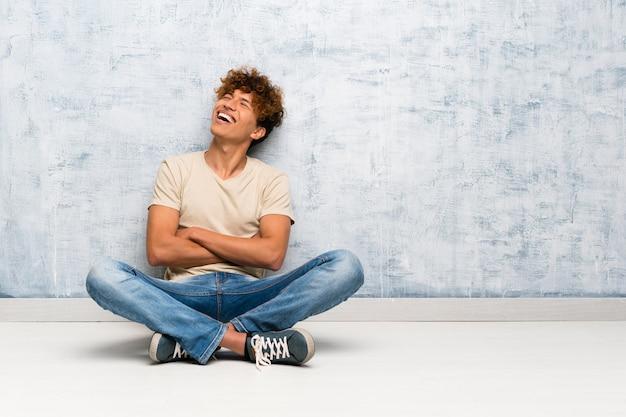 Jovem, homem americano africano, sentar chão, com, braços cruzaram, e, feliz