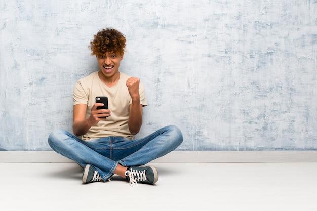 Jovem, homem americano africano, sentar chão, com, telefone, em, posição vitória