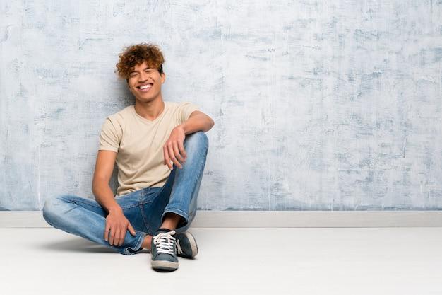 Jovem, homem americano africano, sentar chão, mantendo, a, braços cruzaram, em, frontal, posição