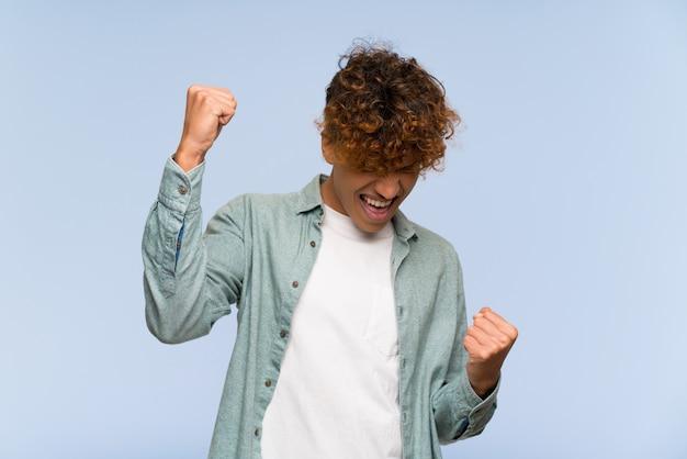 Jovem, homem americano africano, sobre, isolado, parede azul, celebrando, um, vitória