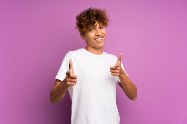 Jovem, homem americano africano, sobre, isolado, parede roxa, apontar, frente, e, sorrindo
