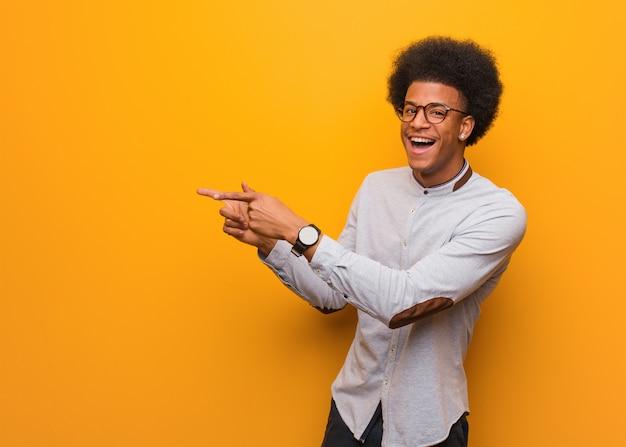 Jovem, homem americano africano, sobre, um, laranja, parede, apontar, ao lado, com, dedo