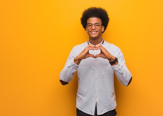 Jovem, homem americano africano, sobre, um, laranja, parede, fazendo, um, forma coração, com, mãos