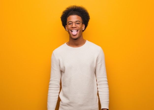 Jovem, homem americano africano, sobre, um, laranja, parede, funnny, e, amigável, mostrando, língua