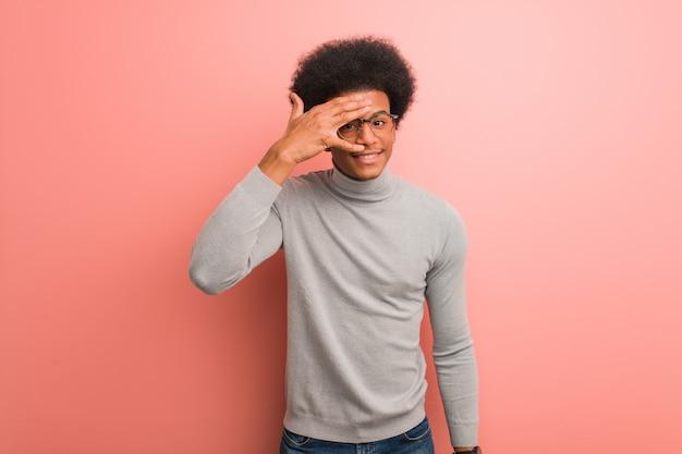 Jovem, homem americano africano, sobre, um, parede cor-de-rosa, envergonhado, e, rir, ao mesmo tempo