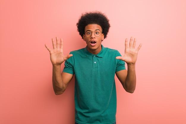 Jovem, homem americano africano, sobre, um, parede cor-de-rosa, mostrando, numere dez