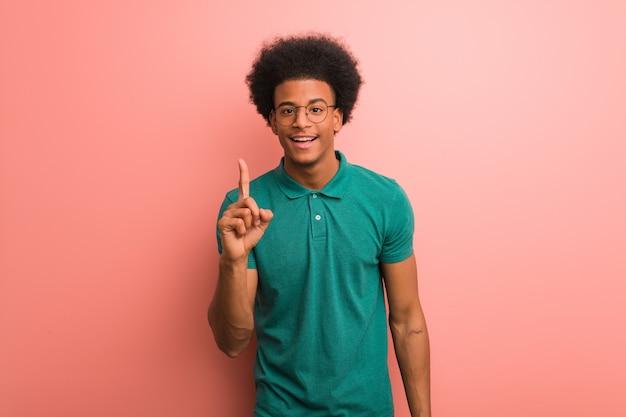 Jovem, homem americano africano, sobre, um, parede cor-de-rosa, mostrando, numere um