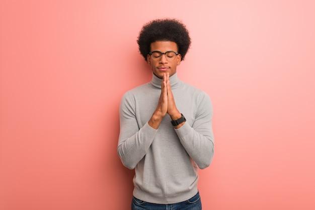 Jovem, homem americano africano, sobre, um, parede cor-de-rosa, orando, muito, feliz, e, confiante