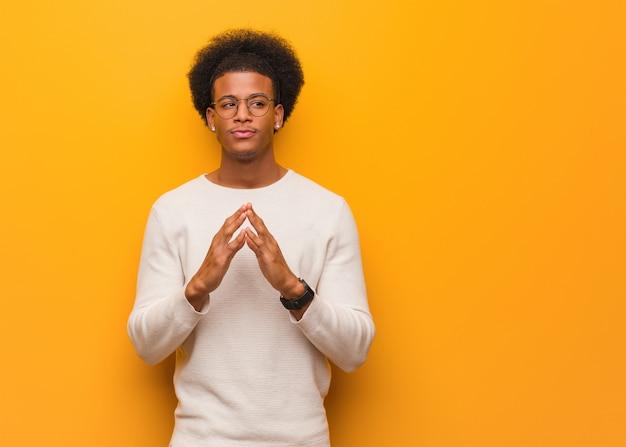 Jovem, homem americano africano, sobre, um, parede laranja, inventar um plano