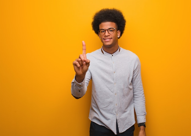 Jovem, homem americano africano, sobre, um, parede laranja, mostrando, numere um