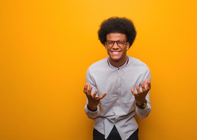 Jovem, homem americano africano, sobre, um, parede laranja, zangado, e, virada