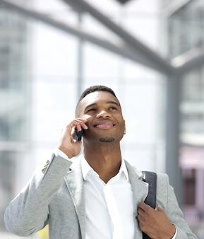 Jovem, homem americano africano, sorrindo, com, telefone móvel