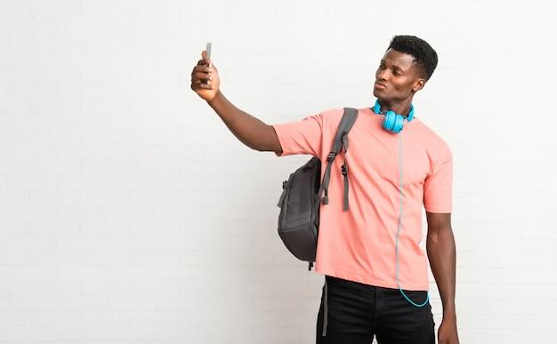 Jovem, homem americano afro, estudante, fazendo, um, selfie