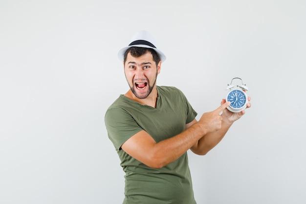 Jovem homem apontando para o despertador com camiseta verde, chapéu e cara de louco
