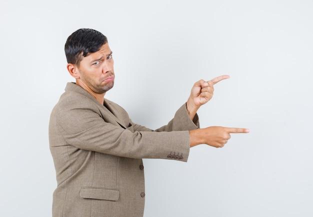 Jovem homem apontando para o lado em uma jaqueta marrom acinzentada, camisa preta e parecendo descontente.
