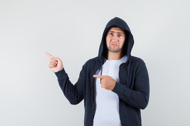 Jovem homem apontando para o lado esquerdo em camiseta, jaqueta e parecendo triste. vista frontal.
