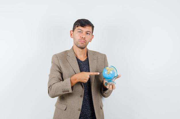 Jovem homem apontando para o mini globo em uma jaqueta marrom acinzentada, camisa preta e olhando com foco, vista frontal.