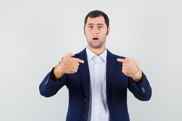 Jovem homem apontando para si mesmo em camisa, jaqueta e parecendo perplexo