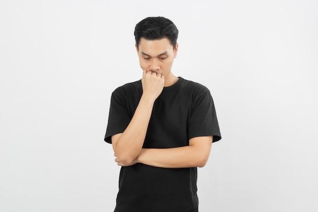 Jovem homem asiático bonito com camisa preta infeliz com a mão, cobrindo a boca isolada no branco