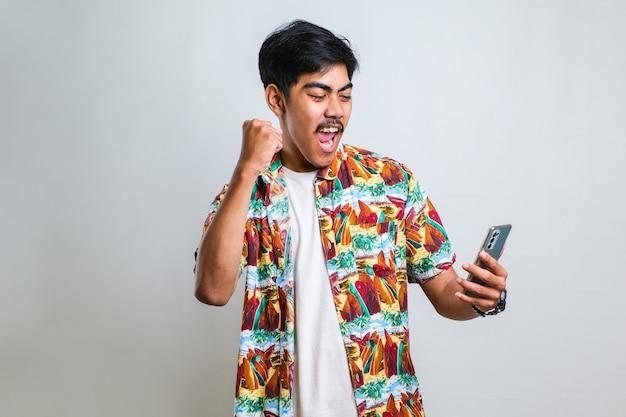 Jovem homem asiático posando de jogos de jogo de fundo branco isolado por telefone faz o gesto de vencedor.