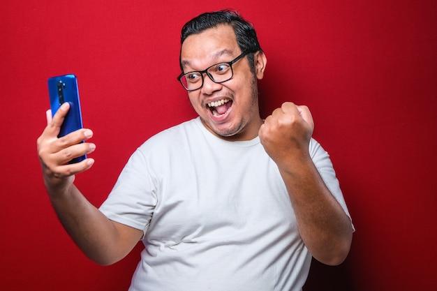 Jovem homem asiático posando de jogos de jogo de fundo vermelho isolado por telefone faz o gesto de vencedor.