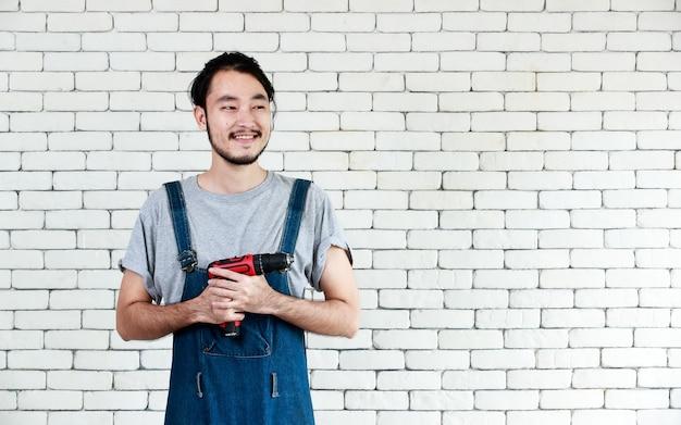 Jovem homem asiático segurando a furadeira em frente a uma parede de tijolos brancos, sorrindo e olhando para a câmera em um fundo de parede de tijolos brancos. , conceito para casa faça você mesmo