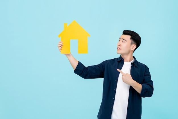 Jovem, homem asiático, segurando, e, apontar, casa, recorte