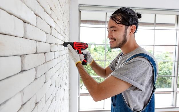 Jovem homem asiático usando furadeira elétrica na parede de tijolo branco na sala, conceito para melhoria em casa, trabalho de bricolage, faça você mesmo.