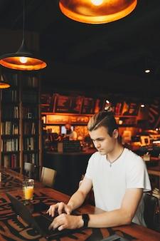 Jovem homem atraente com cabelo comprido em uma camisa branca casual sentado com um copo de suco na mesa de madeira com motivos étnicos e digitando no laptop em um bar escuro com fundo de lâmpadas laranja