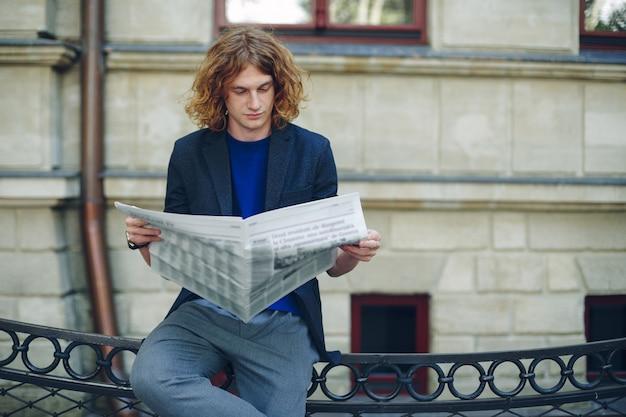 Jovem homem avermelhado lendo jornal perto de edifício de estilo antigo