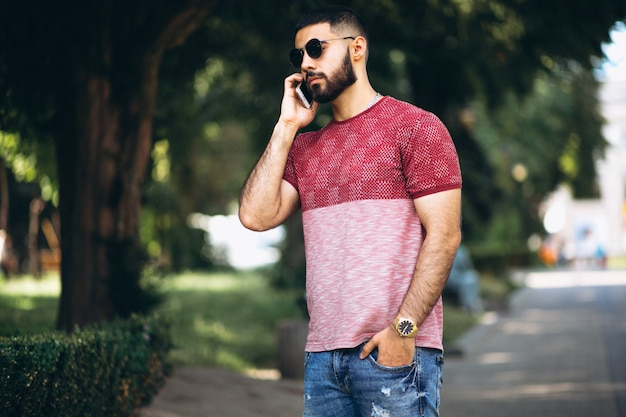 Jovem homem barbudo bonito com telefone
