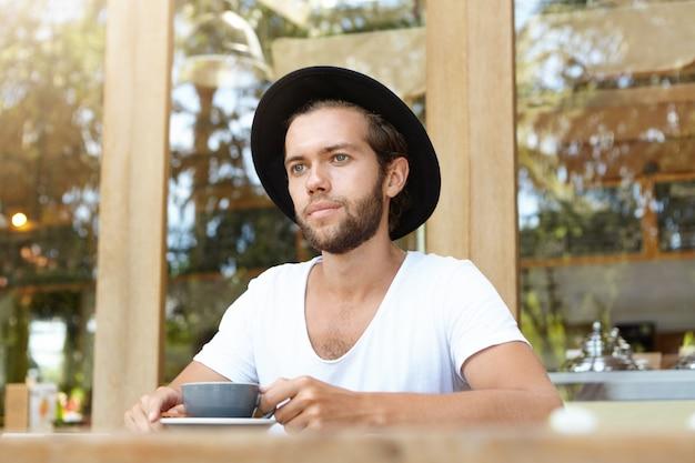 Jovem homem barbudo caucasiano com chapéu elegante tendo cappuccino, sentado à mesa de madeira com caneca no café ao ar livre
