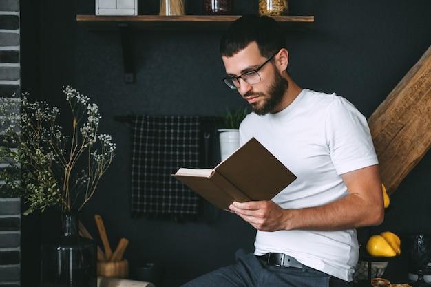 Jovem homem barbudo caucasiano lendo um livro na cozinha. lazer em casa.