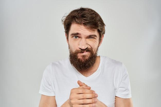 Jovem homem barbudo com expressão de descontentamento