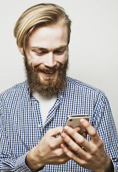 Jovem homem barbudo com telefone móvel