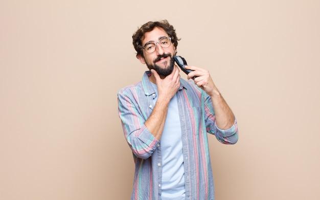 Jovem homem barbudo com um barbeador elétrico