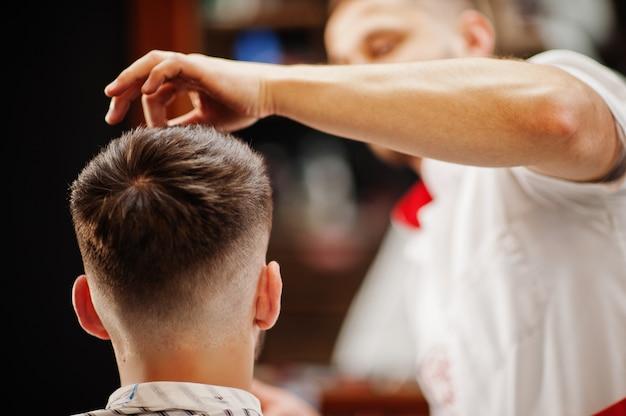 Jovem homem barbudo cortando cabelo de cabeleireiro enquanto está sentado na cadeira de barbearia. alma de barbeiro.