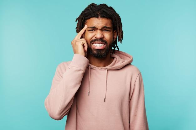 Jovem homem barbudo de cabelos escuros descontente fazendo uma careta e segurando o dedo na têmpora enquanto olha para a câmera, em pé sobre um fundo azul em roupas casuais