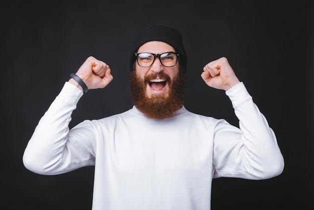 Jovem homem barbudo está gritando e segurando as duas mãos perto da parede preta.